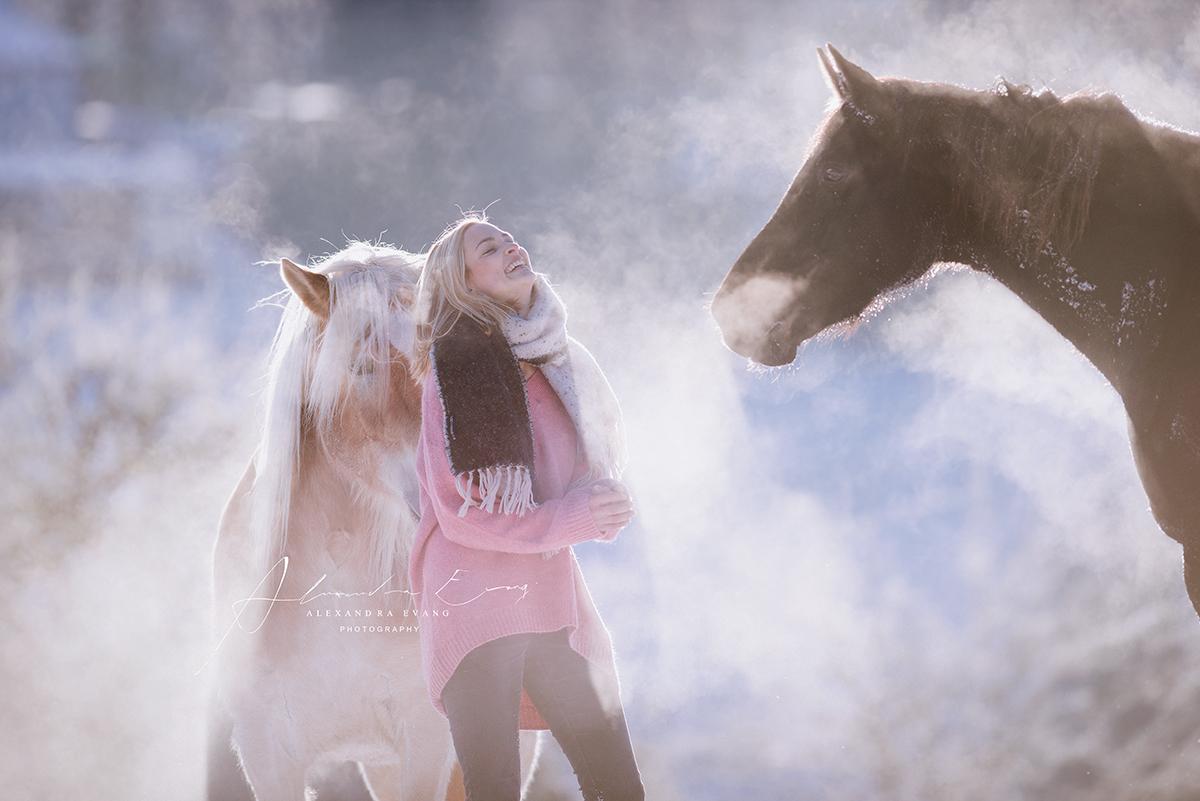 Pferde und eine lächelnde Frau im Schnee.